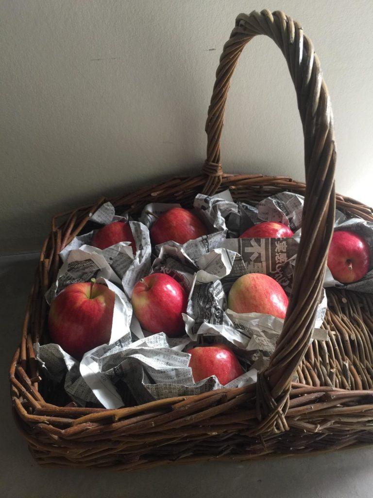 一つずつ新聞紙にくるまれてカゴに入っているスリムなリンゴ