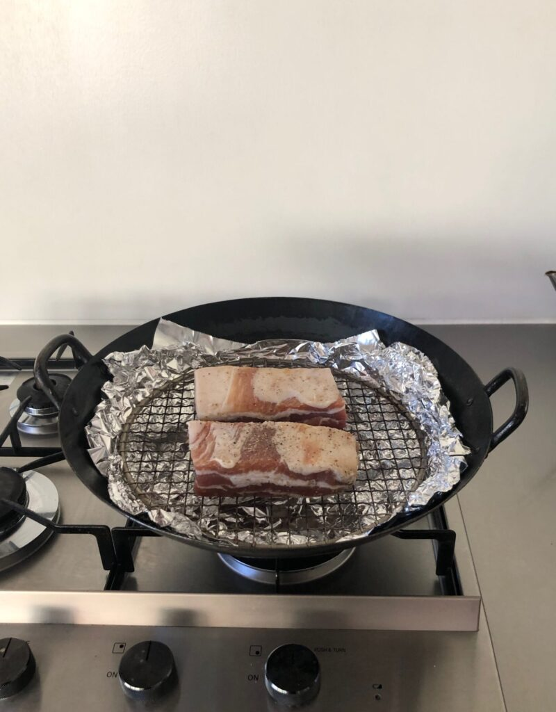 中華鍋にチップをしき網を置いて豚バラ肉をのせる