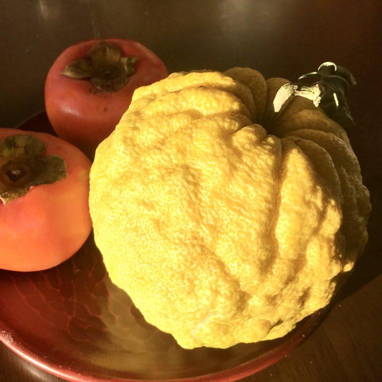 鬼柚子と柿がテーブルにのっている