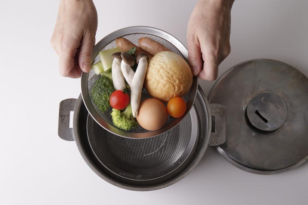 パン、卵、野菜を並べた浅ざるを、鍋中の小ざるの上にのせて蒸します。