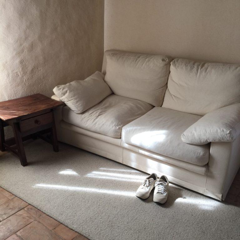 漆喰の壁の前に白のソファが置いてある