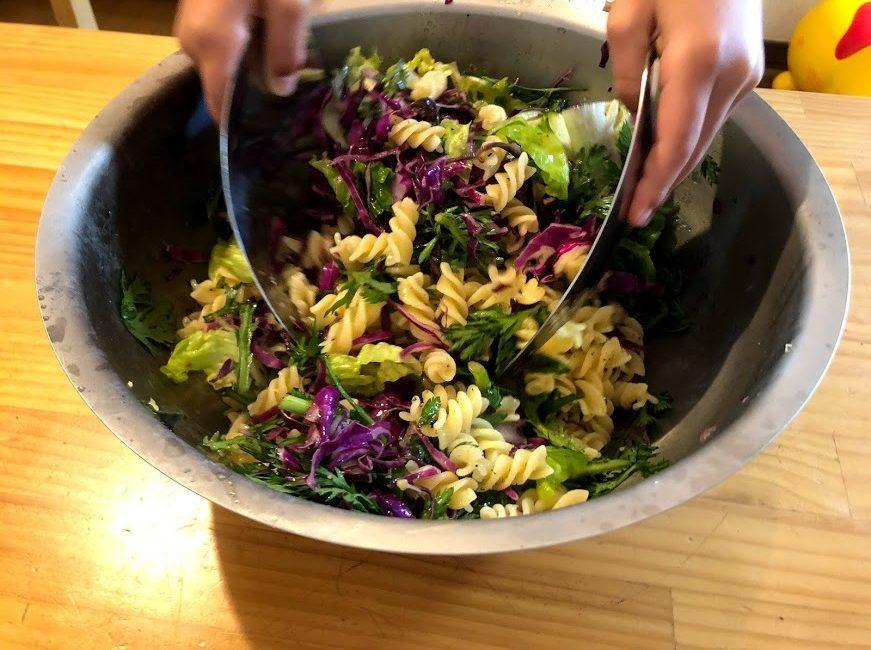 有元葉子のサラダハンドを使って子どもがサラダペンネを混ぜているところ